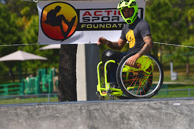 A manual wheelchair user is shown, gliding parallel to the lip of a ramp, waiting to drop in. He is wearing a bright green, motorcycle helmet, which matches the bright green frame of his wheelchair.
