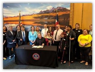 Governor Polis signs SB19-202 as NFBCO members and bill sponsors look on