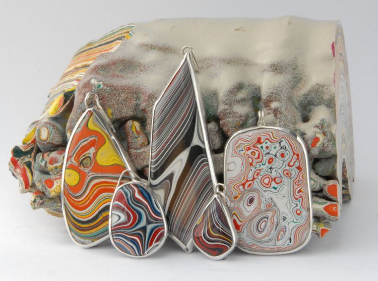 Fordite Pendants set in Silver by Sasha Garrett, against a fordite backdrop