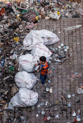 A boy in jeans and an orange shirt standing over large trash bags, surrounded by cans and waste.