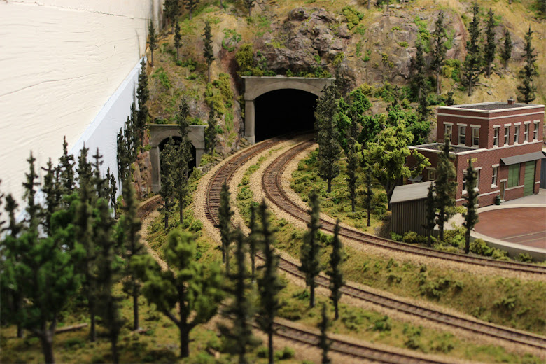 Three curved railroad tracks emerge from a single and double tunnel portal in a mountain forest scene