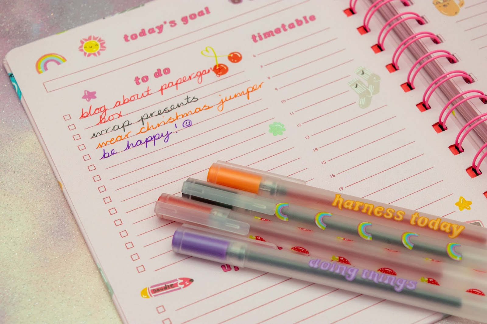 A purple, red, orange and black pen on top of a notebook and writing in each pen.