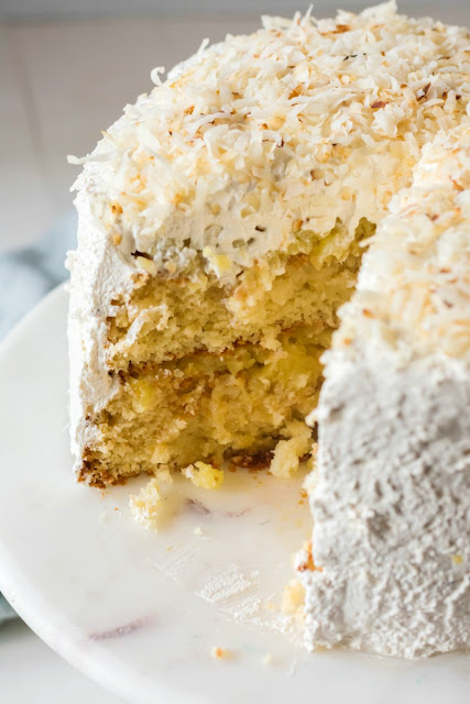 haleakala cake with layers of white cake, pineapple filling, Italian meringue frosting and coconut