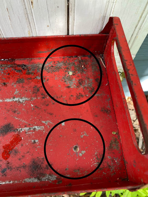 Photo of holes drilled into a metal tray for drainage