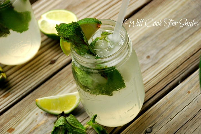 mint mojito in a mason jar with lime and mint and a straw on sitting on a piece of wood
