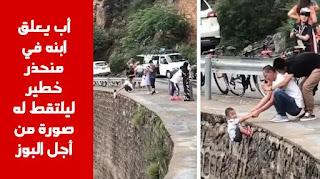 أب يعلق ابنه في منحذر جبلي خطير ليلتقط له صورة من أجل خلق البوز