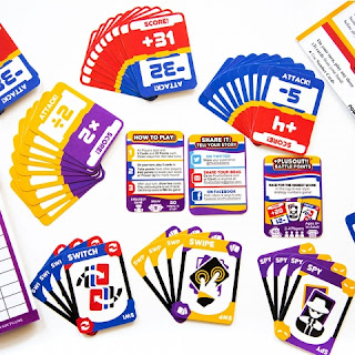 A number of stacks of colourful cards of various types, some containing icons, some containing text, and some containing numbers with mathematics operators like plus and minus signs.