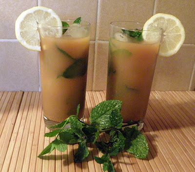 Two Glasses of Tea Garnished with Lemon and Mint