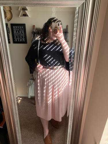 A mirror selfie of an outfit of a black bell sleeve blouse tucked into a pink pleated skirt and d'orsay flats.