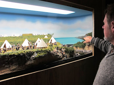 A man poses in front of a diorama of an encampment of 19th-century soldiers by the sea.