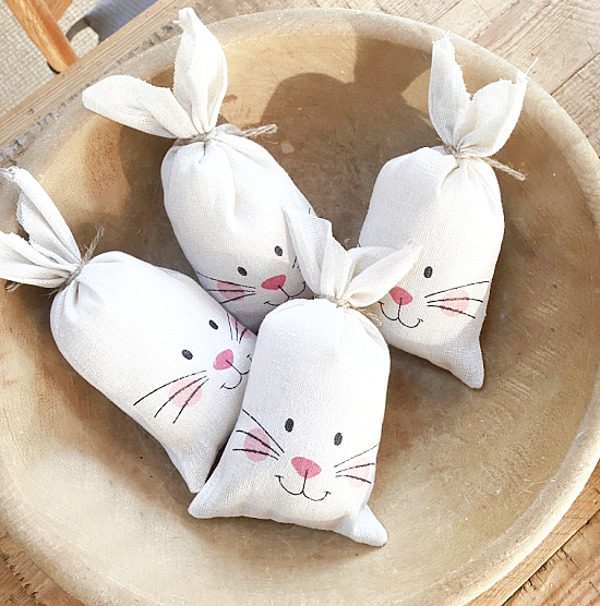 wooden bowl with 4 stuffed bunnies