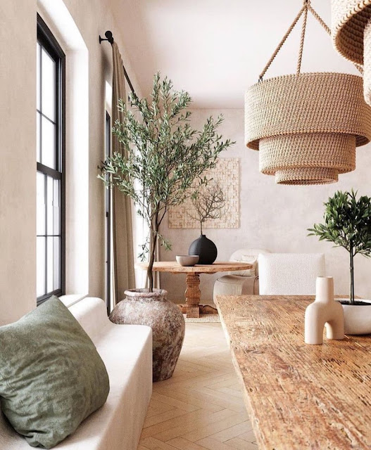 neutral sculptural vase on top of distressed dining table in bohemian dining room