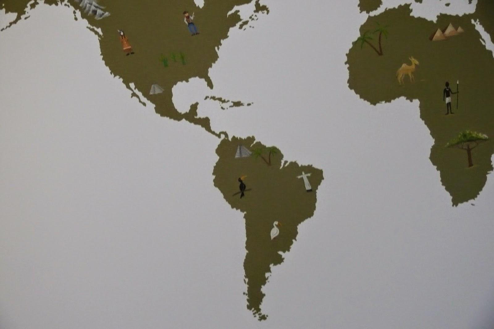 Malowanie n ścianie w pokoju dziecięcym prostej grafiki przedstawiającej mapę świata