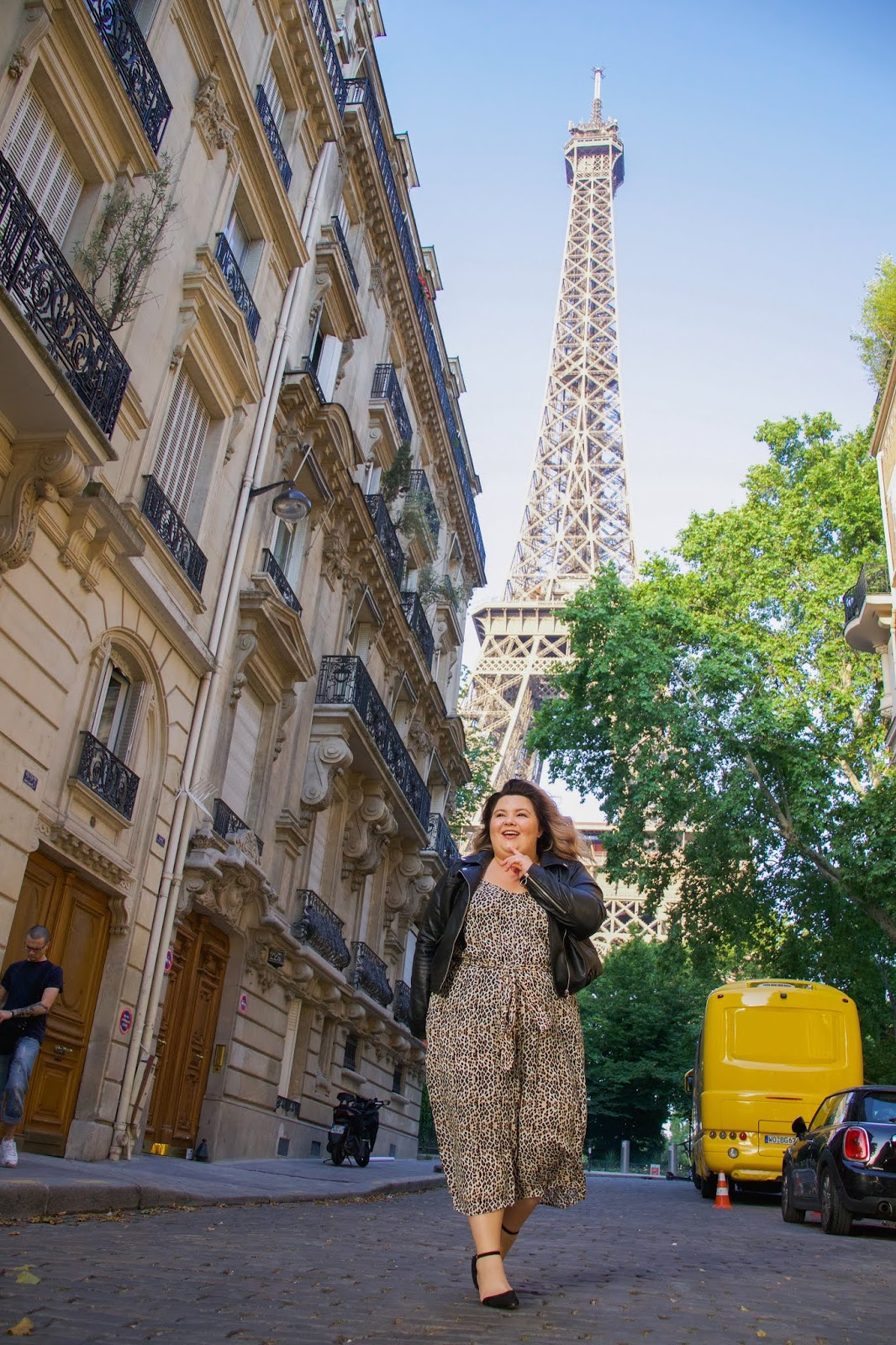 Chicago Plus Size Petite Fashion Blogger, influencer, YouTuber, and model Natalie Craig, of Natalie in the City, wears Chic Soul's Make A Scene Leopard Jumpsuit in Paris while visiting Rue de l'Université street in front of the Eiffel Tower.