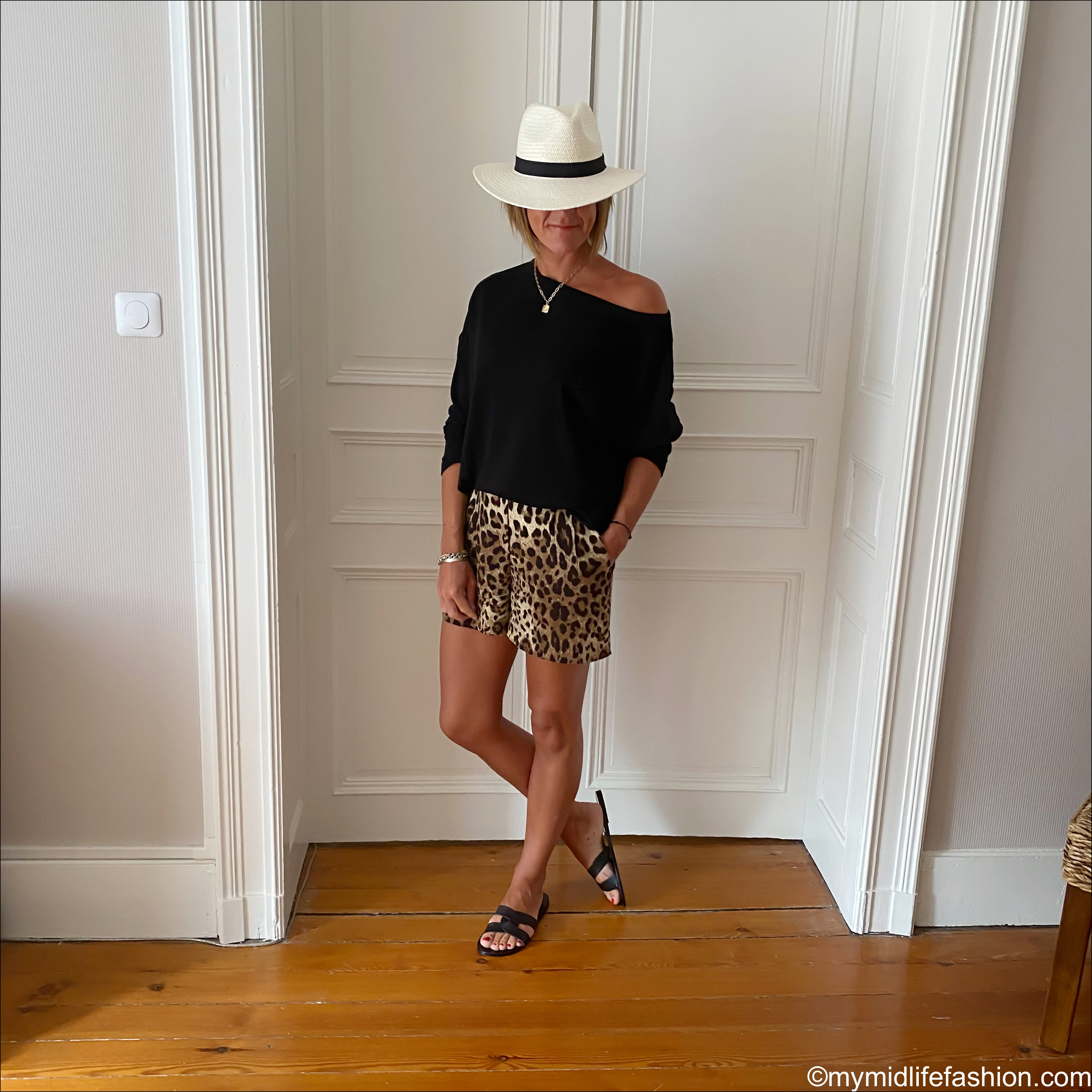 my midlife fashion, ancient greek desmos leather slides, all saints Rita off the shoulder t shirt, dolce and Gabbana leopard print shorts, zara Panama hat