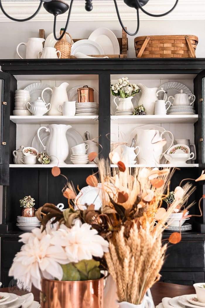 dried wheat and grasses in vintage vessels, black hutch filled with ironstone pitchers, dishes, platters and cups