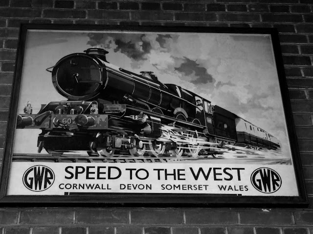 Black and White photo of the Great Western Railway iconic poster 'Speed To The West' on display at Leamington Spa railway station