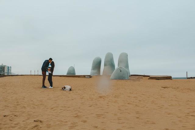 Casal se beijando em frente aos dedos que saem da areia
