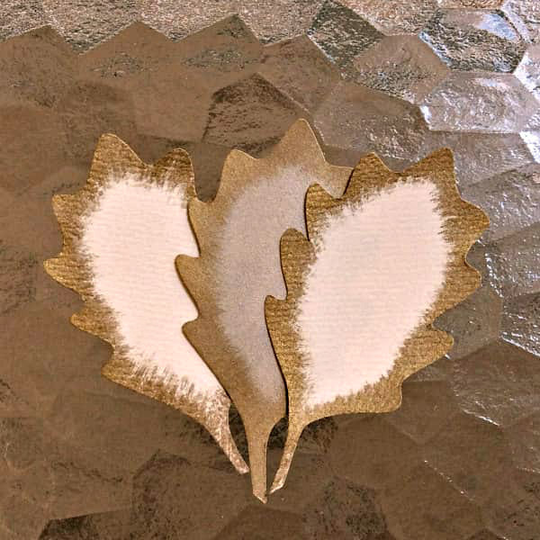 three paper oak leaves with gold paint brushed edges