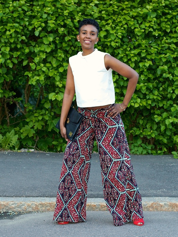 woman in white top and african print palazzo pants with right hand on waist