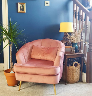 dark navy blue walls with a blush pink velvet tub chair