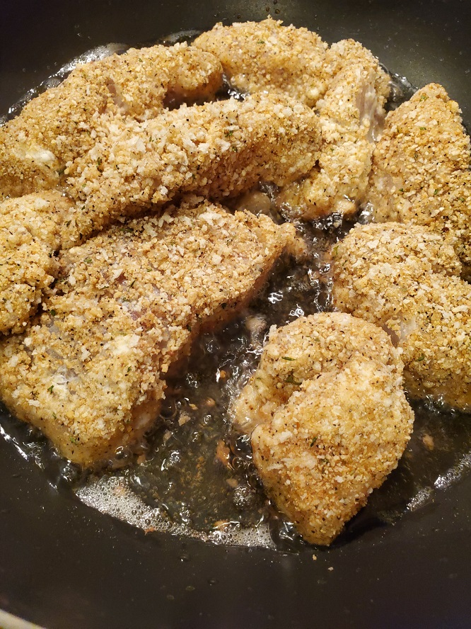 This is freshly caught snook frying in a pan of oil that is coated with cracker crumbs