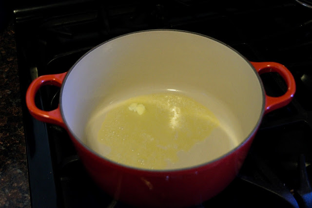 A pot, on the stove, with butter melting in it.
