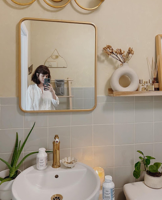 white modern donut vase on display in neutral bathroom