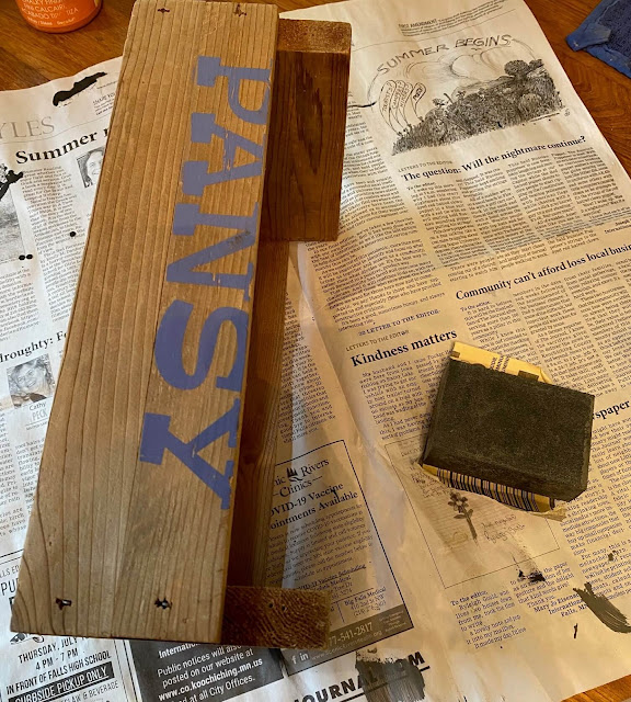 Photo of a word stenciled on a crate being sanded off