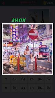 на улице города стоит девушка вечером под знаком стоп на тротуаре