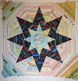 Four right triangles of string pieced light value fabrics add to the previous octagonal shape to make a square quilt of many string pieced diamonds.