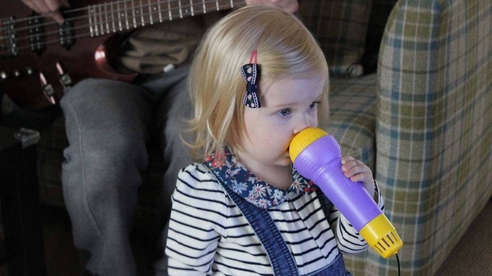 My two year old stood up singing in to a toy microphone. my husband is sat on the sofa behind her playing his bass guitar.