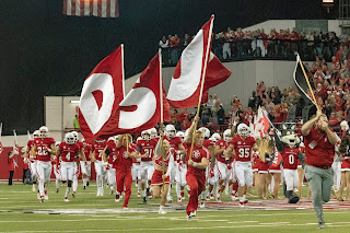 USD coyote football players in red and white run across a field as red and white cheerleaders carrying flags with the letters U, S, and D run alongside them.