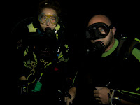 2 divers have their photos taken night diving