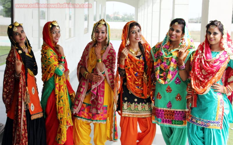 Students in Traditional Punjabi dress pose for a photograph during Teej celebrations at Bajaj College