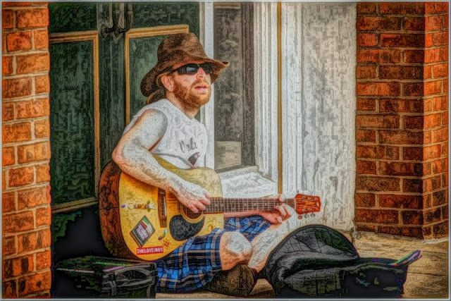 Street performer playing guitar and wearing cowboy hat and sunglasses