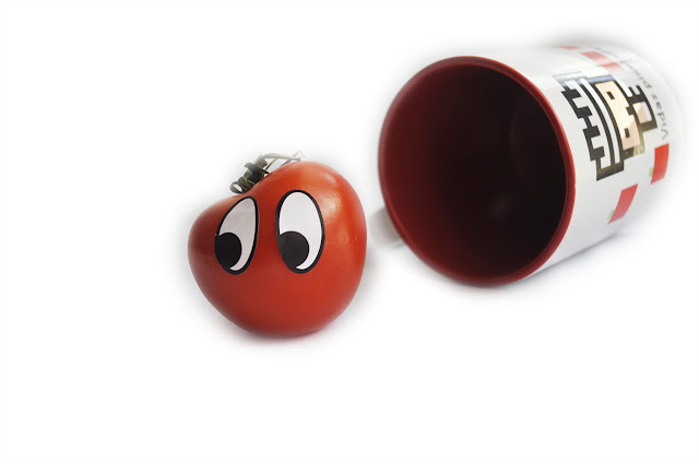 un tomate con pegatinas de ojos, parece salir de una taza tumbada  blanca con logo de vidas pixeladas, con interior rojo