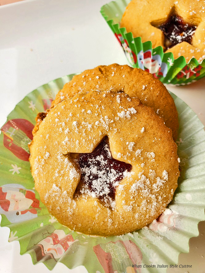 these are jam filled cookies sprinkled with powdered sugar called Linzer cookies there is a star cut out of the middle of the cookie with raspberry jam peeking through it