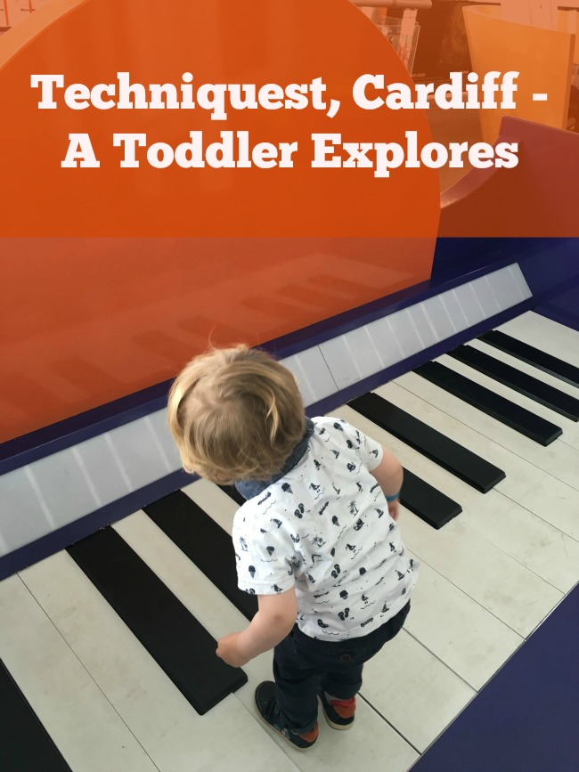 Techniquest-Cardiff-A-Toddler-Explores-text-on-image-of toddler-standing-on-giant-keyboard