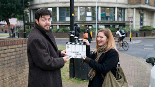Tom Burke and Holliday Grainger outside behind the scenes with a clapperboard