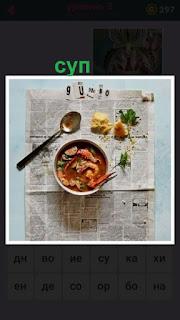 на столе на газете стоит миска с супом и рядом ложка лежит