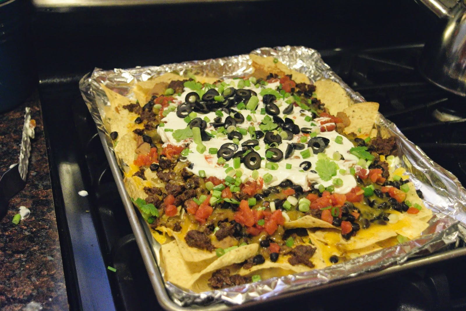 The Nachos Supreme being topped with sour cream, chopped scallions, and sliced black olives.