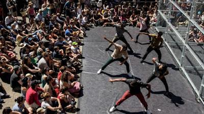 Föreställningen D-Construction med sex dansare på scen med byggnadsställning till höger och publik runt om scenen.