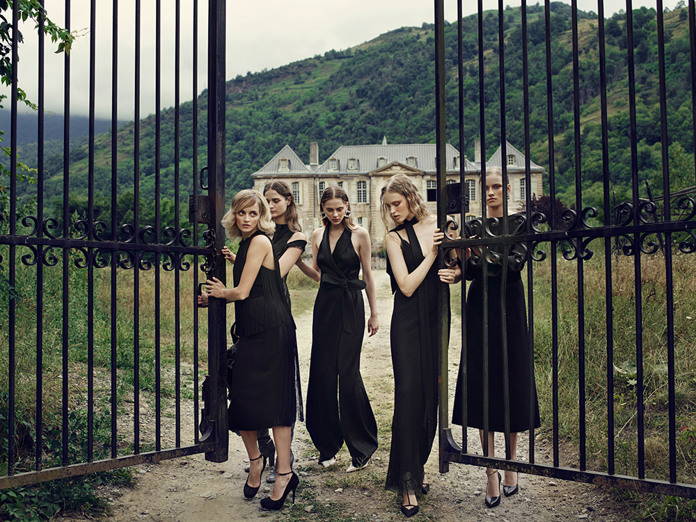 Models in black at gates outside of decaying French Chateau Gudanes