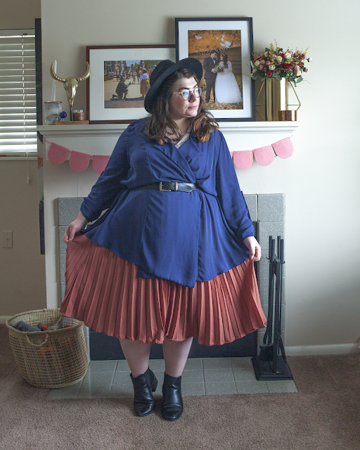 An outfit consisting of a wide brim black fedora, navy blue structureless trench belted over of a dusty rose colored pink pleated skirt.