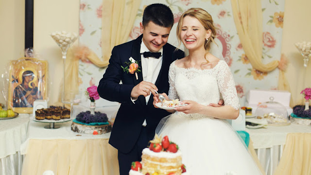 bride and groom in front of desserts