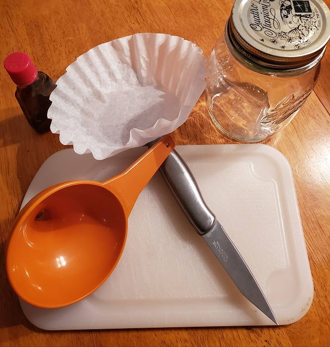 this is the tools you will need when making homemade vanilla extract. Mason jars, coffee filters, clean bottles, strainer and funnel along with a cutting board and knife