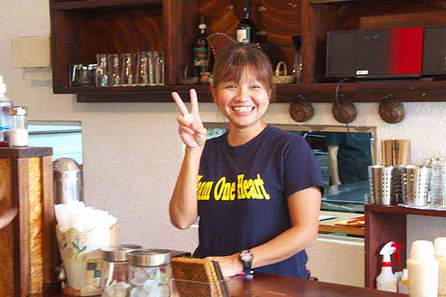 smiling waitress giving peace sign