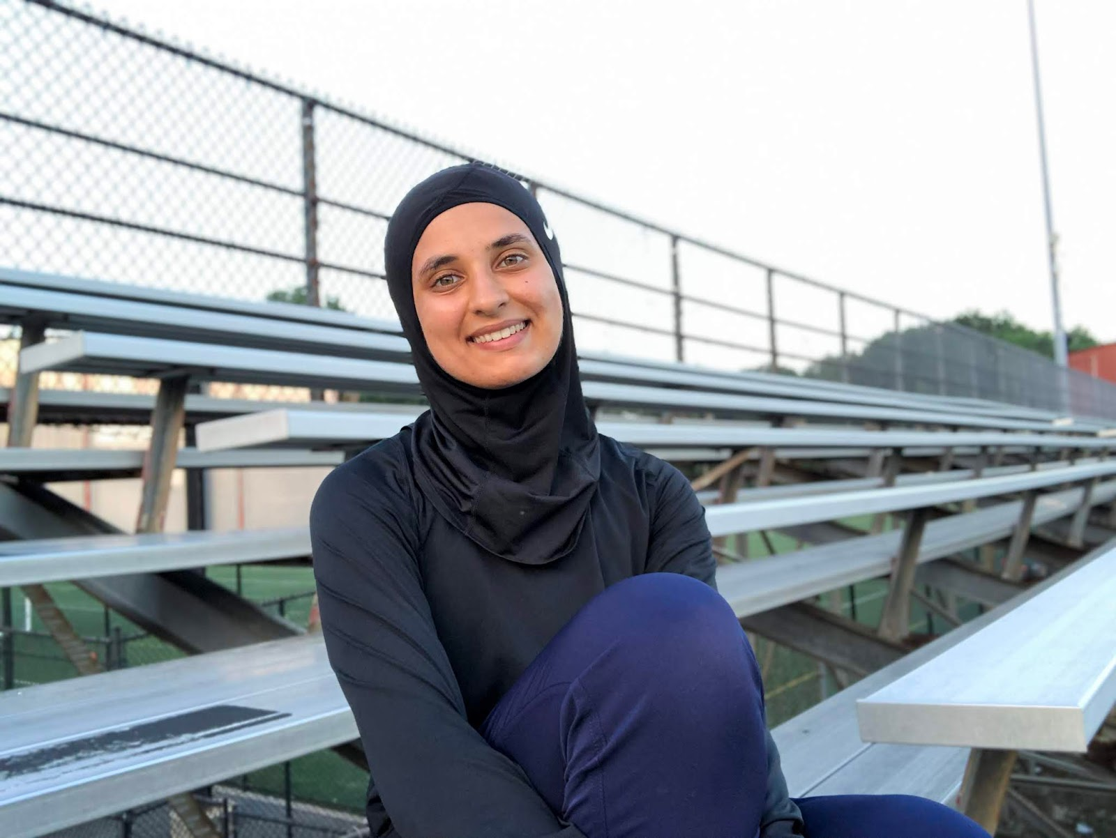 Sahara sitting on a bench at the track, smiling at camera in black nike hijab