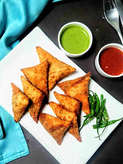 Serving onion samosa in s plate with fried green chili. Green chutney and sweet chutney in background